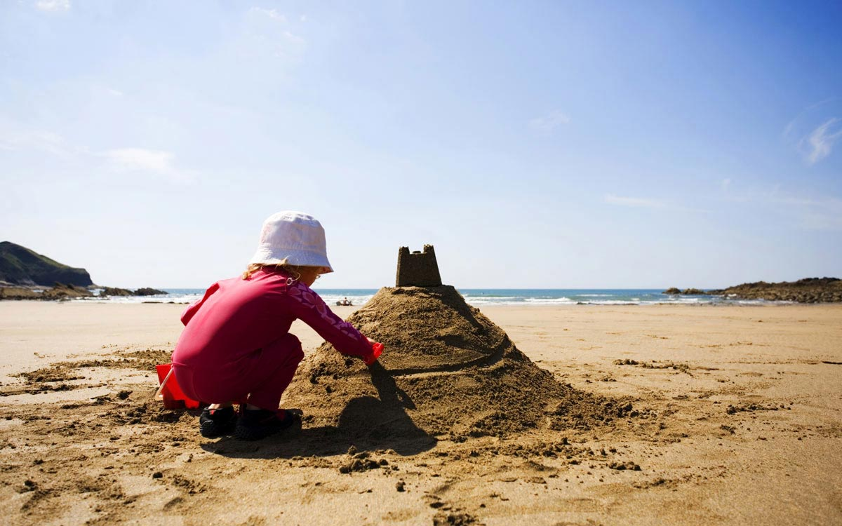 Little girl building a sandcastle at Crackington Haven beach, North Cornwall